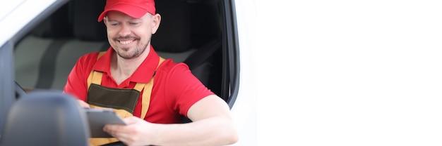 Courrier d'homme en uniforme assis au volant d'une voiture avec une tablette numérique dans les mains. notion de logistique