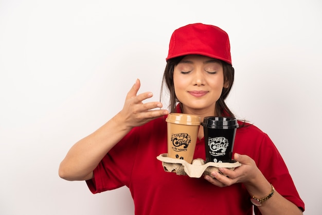 Courrier de la jeune femme renifle le café arôme pour la livraison sur fond blanc