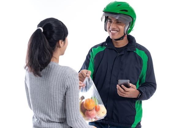 Courrier de livraison asiatique livrant de la nourriture à une cliente isolée sur fond blanc