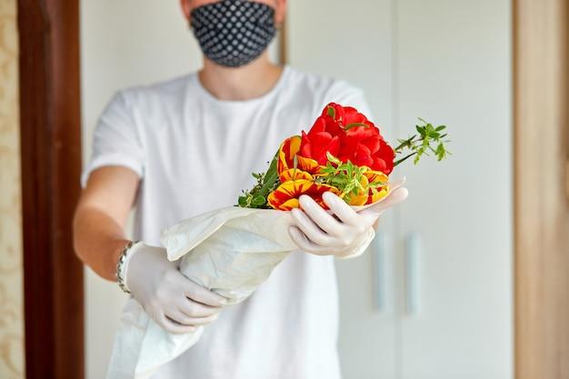 Courrier, livraison en blanc dans des gants médicaux livre en toute sécurité les achats en ligne un bouquet de fleurs