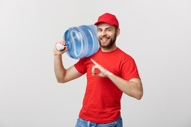 Courrier de livraison de l'eau embouteillée dans le t-shirt rouge et le cap transportant le réservoir de boisson et de pointage