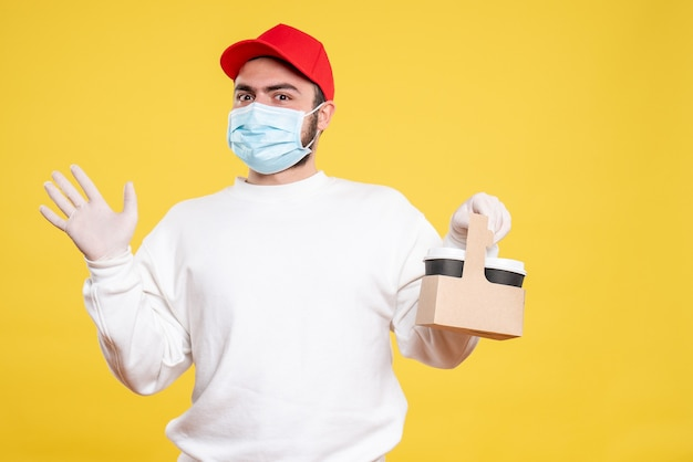Courrier mâle en masque tenant un café de livraison sur jaune
