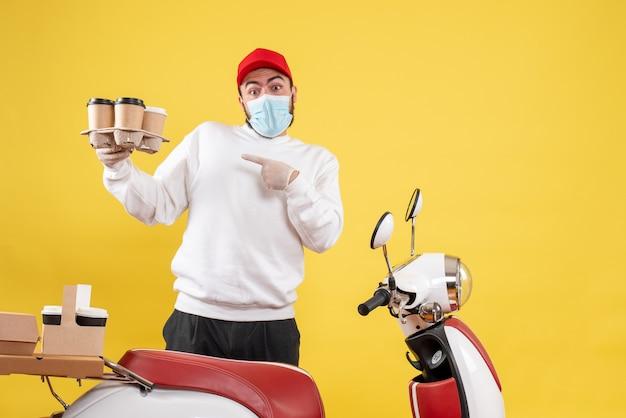 Courrier mâle en masque tenant du café sur jaune