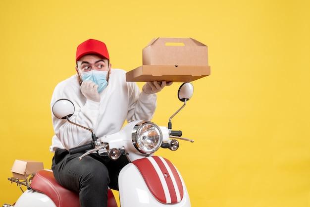 Courrier mâle en masque sur vélo tenant une boîte de nourriture sur jaune