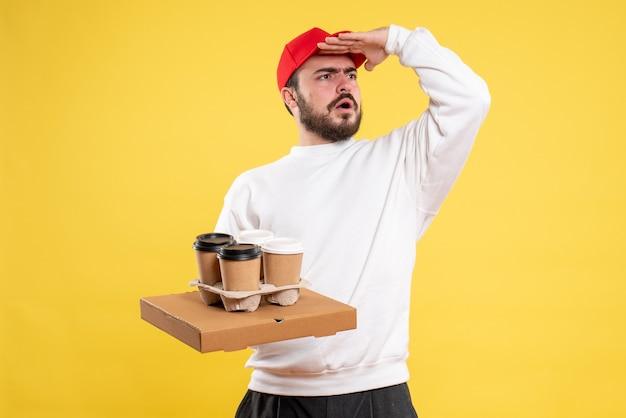 Courrier mâle tenant une boîte de livraison de nourriture et du café sur jaune