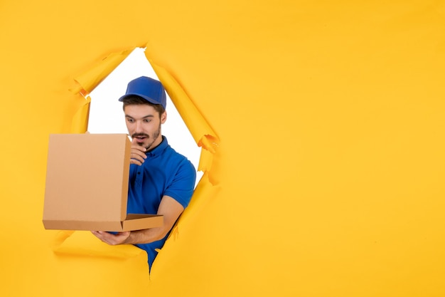 Courrier mâle vue de face tenant une boîte à pizza sur un espace jaune