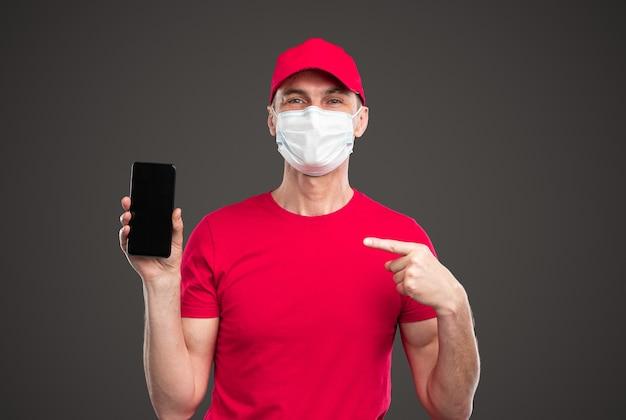 Courrier masculin amical en uniforme rouge et masque de protection montrant un smartphone avec écran noir tout en recommandant un service de livraison en ligne pendant la pandémie de coronavirus