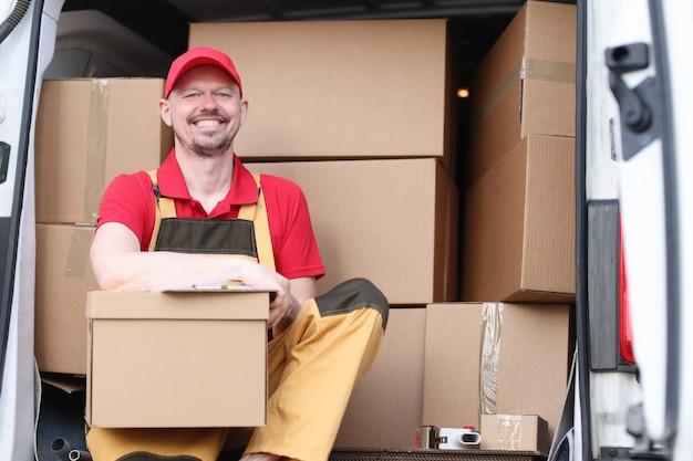 Courrier masculin assis dans une voiture avec des boîtes en carton et des documents
