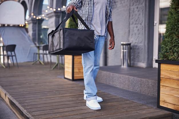 Courrier masculin en chemise à carreaux et jeans tenant un sac d'emballage thermique isolé