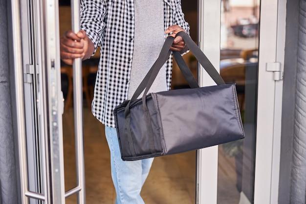 Courrier masculin en chemise à carreaux tenant un sac d'emballage thermique isolé tout en quittant la pizzeria