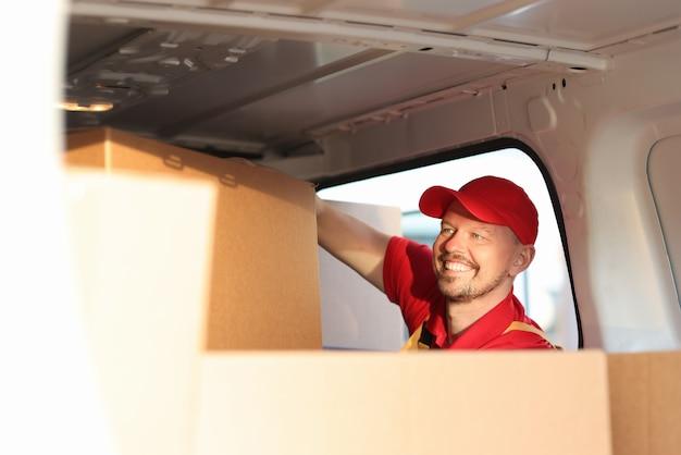 Courrier masculin mettant des boîtes en carton dans la voiture