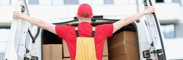 Courrier masculin ouvrant une voiture de mini-fourgonnette avec de nombreuses boîtes en carton