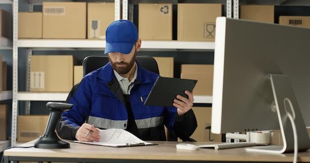 Courrier masculin remplissant la facture et saisissant les données tout en appuyant sur l'écran de l'ordinateur