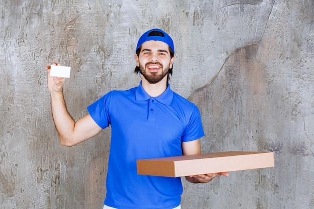 Courrier masculin en uniforme bleu portant une boîte en carton et présentant sa carte de visite.