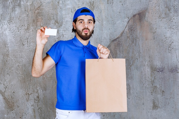 Courrier masculin en uniforme bleu tenant un sac en carton et présentant sa carte de visite.