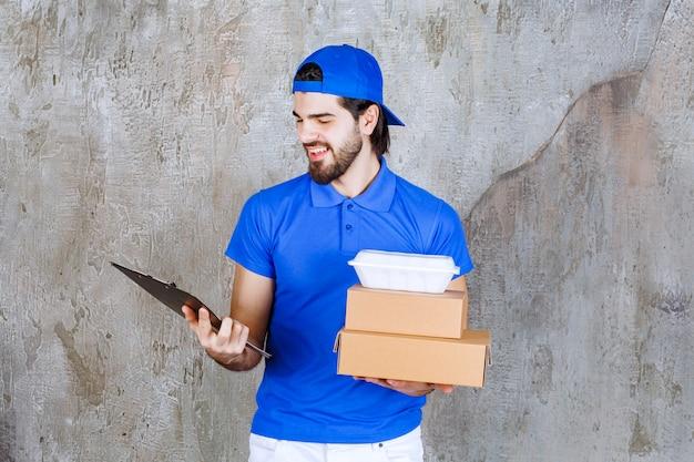 Courrier masculin en uniforme bleu transportant des boîtes en carton et en plastique et vérifiant l'adresse du nom du client