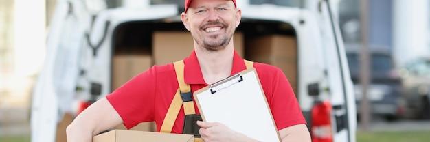 Le courrier masculin en uniforme tient le presse-papiers et la boîte en carton en arrière-plan du camion avec des boîtes