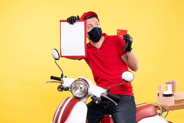 Courrier masculin vue de face dans un masque tenant une note de fichier et une carte bancaire sur jaune