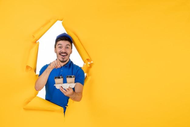 Courrier masculin vue de face en uniforme bleu tenant des tasses à café sur un espace jaune