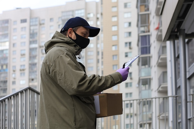 Courrier en masque facial avec un colis à l'entrée de la maison vérifie les informations contenues dans les documents.