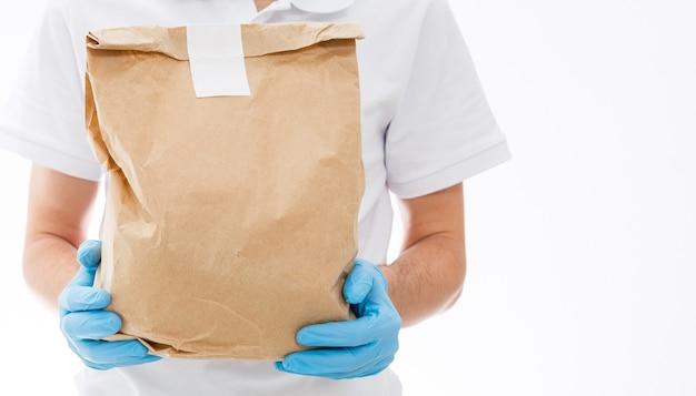 Courrier en masque de protection et gants médicaux livre des plats à emporter. service de livraison en quarantaine, épidémie de maladie, conditions de pandémie de coronavirus covid-19.