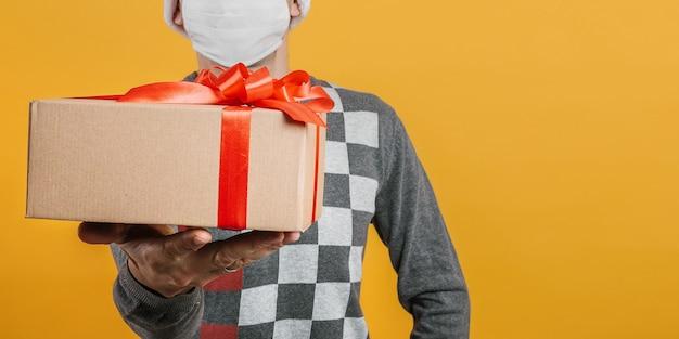 Un courrier offre un cadeau la veille de noël dans un masque du coronavirus