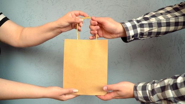 Le courrier passe un colis artisanal avec le produit à l'acheteur