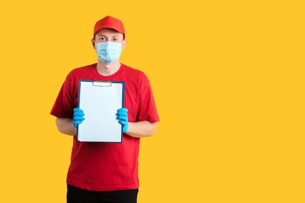 Un courrier portant un masque et des gants dans un uniforme rouge montre un presse-papiers comme un presse-papiers sur jaune