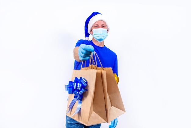 Courrier en uniforme bleu, masque médical de protection, gants et chapeau de père noël détient des sacs-cadeaux