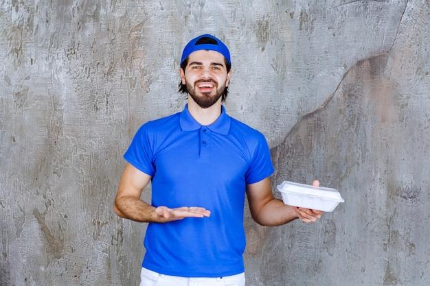 Courrier en uniforme bleu tenant une boîte à emporter en plastique.