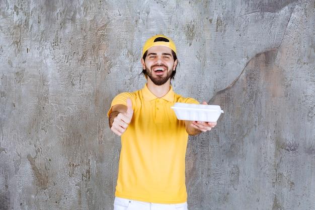 Courrier en uniforme jaune livrant une boîte à emporter en plastique et montrant un signe positif de la main.
