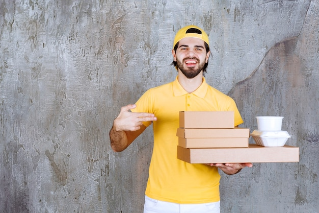 Courrier en uniforme jaune tenant des colis à emporter et des boîtes en carton.