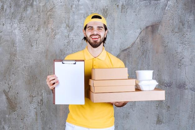 Courrier en uniforme jaune tenant des colis à emporter et un sac à provisions et demandant une signature