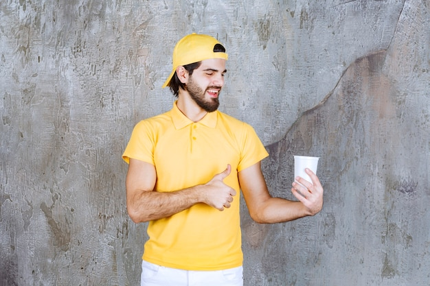 Courrier en uniforme jaune tenant un gobelet jetable et montrant un signe positif de la main.