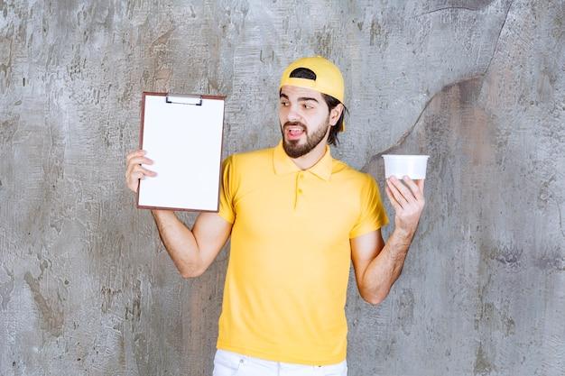 Courrier en uniforme jaune tenant un gobelet en plastique et demandant une signature.