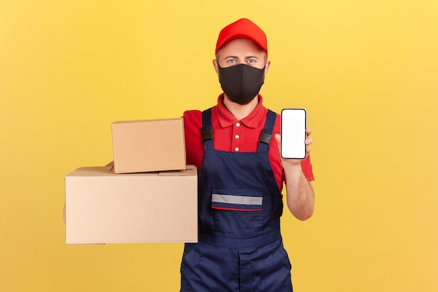 Courrier en uniforme et masque de protection sur le visage tenant et montrant des boîtes en carton et un smartphone