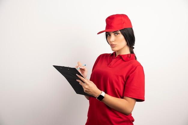 Courrier en uniforme rouge écrit les commandes sur le presse-papiers. photo de haute qualité