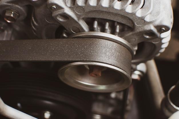 Courroie de distribution de l'ancien alternateur dans le système moteur de la voiture, concept de pièce automobile.