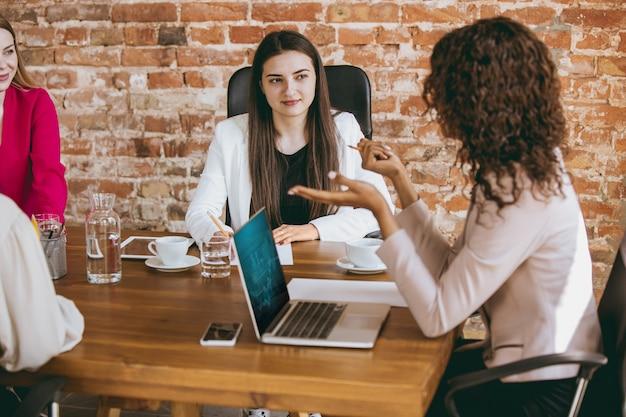 En cours d'analyse. jeune femme d'affaires dans un bureau moderne avec équipe. réunion créative, attribution de tâches. les femmes travaillant au front-office. concept de finance, d'affaires, de pouvoir des filles, d'inclusion, de diversité, de féminisme.