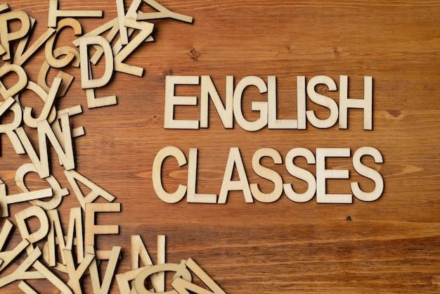 Cours d'anglais de mots faits avec des lettres en bois sur la table de planche blanche