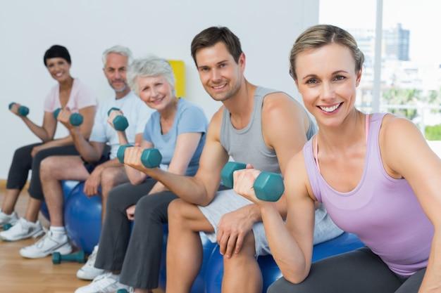 Cours de conditionnement physique, exercice avec des haltères dans la salle de gym