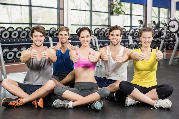 Cours de conditionnement physique montrant les pouces en l'air