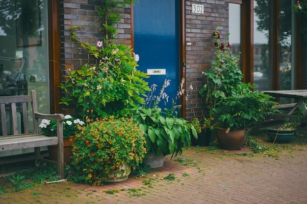 Cours confortables d'amsterdam, bancs, vélos, fleurs dans des bacs.