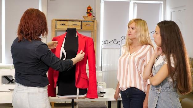 Cours de coupe et couture. la couturière montre aux femmes comment coudre des poches sur des vêtements sur un mannequin. seamster apprend à ses élèves à coudre des vêtements pour montrer des détails sur une veste pendant les cours. entreprise de couture.