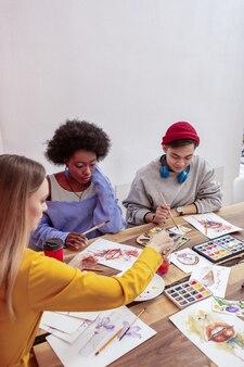 Cours de dessin. trois étudiants en art talentueux à la mode qui fréquentent un cours de dessin ensemble