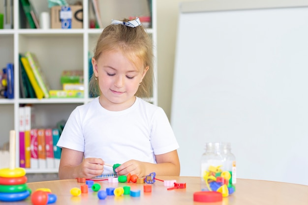 Cours de développement et d'orthophonie avec un enfant. exercices d'orthophonie et jeux avec des perles.
