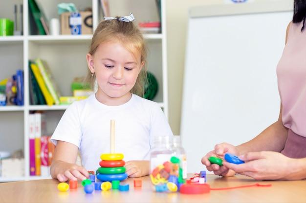 Cours de développement et d'orthophonie avec une enfant-fille. exercices et jeux d'orthophonie avec une pyramide colorée