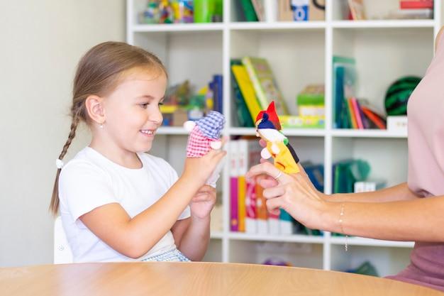 Cours de développement et d'orthophonie avec une enfant-fille. exercices d'orthophonie et jeux de théâtre avec les doigts.