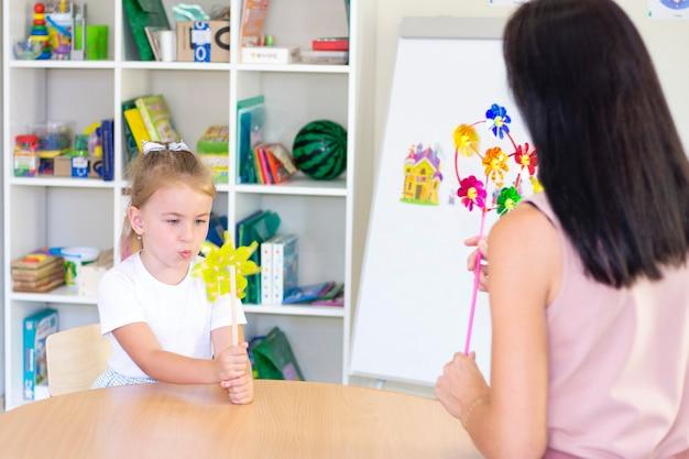 Cours de développement et d'orthophonie avec une enfant-fille. orthophonie et jeux de spinning. fille qui souffle