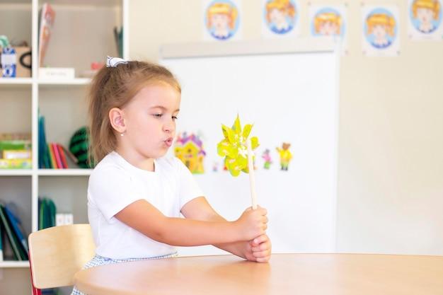 Cours de développement et d'orthophonie avec une enfant-fille. orthophonie et jeux de spinning. fille soufflant
